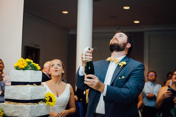 Image of groom popping champagne bottle