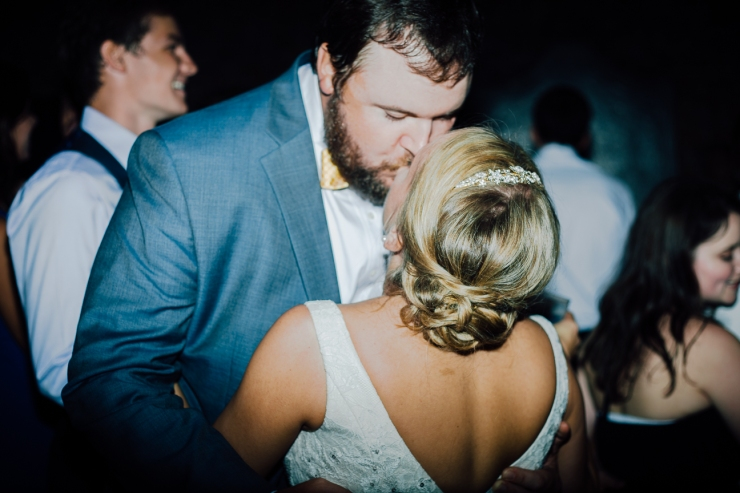 Image of bride and groom sharing a kiss on the dance floor