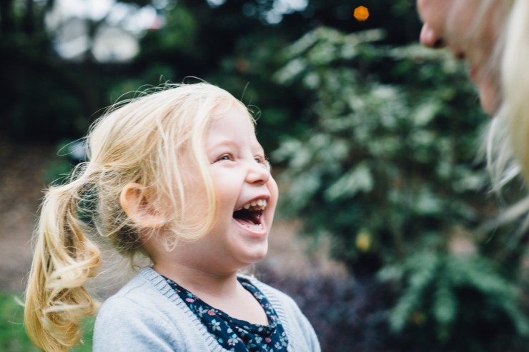 Image of young girl laughing during a family photo shoot in a Greenville SC park