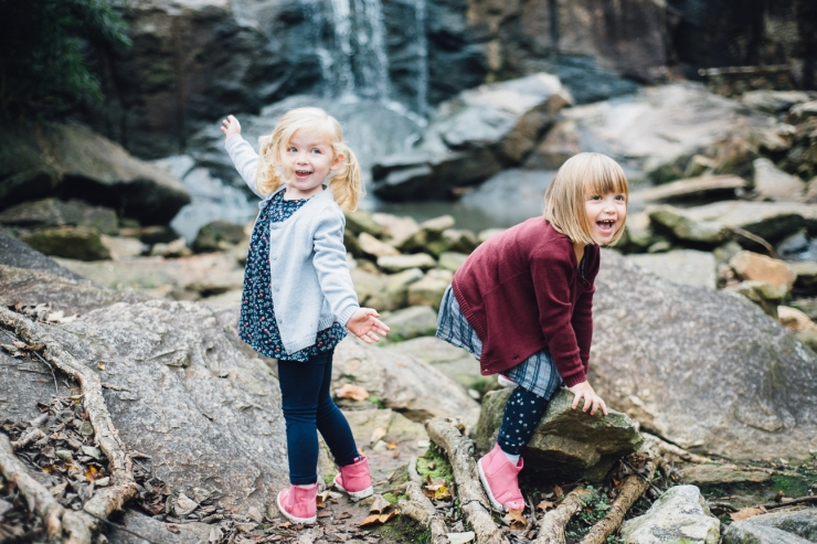Image of little girls climbing on rocks near waterfall