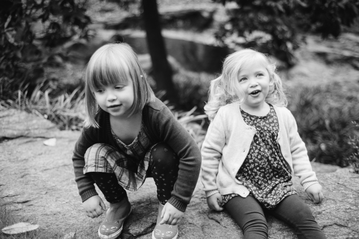 Image of young sisters sitting in the park during family photo shoot