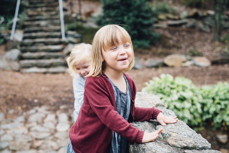 Image of young sisters standing on a bridge during a family photo shoot in a Greenville SC park