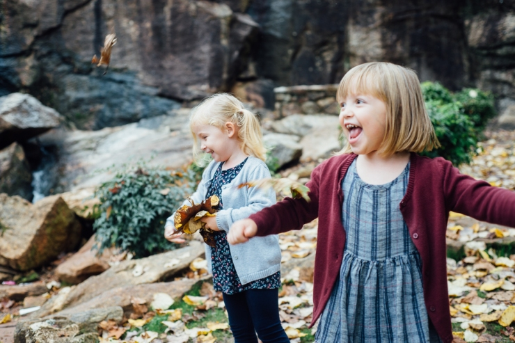 Image of young sisters throwing leaves and laughing during a family photo shoot
