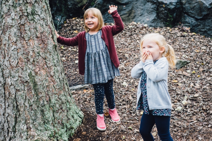 Image of young sisters playing together during a family photo shoot in a Greenville SC park