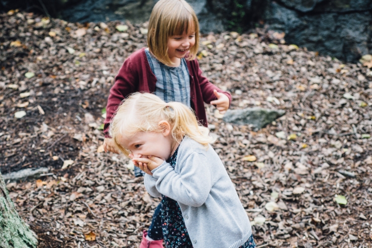 Image of young sisters playing during a family photo shoot in a Greenville SC park