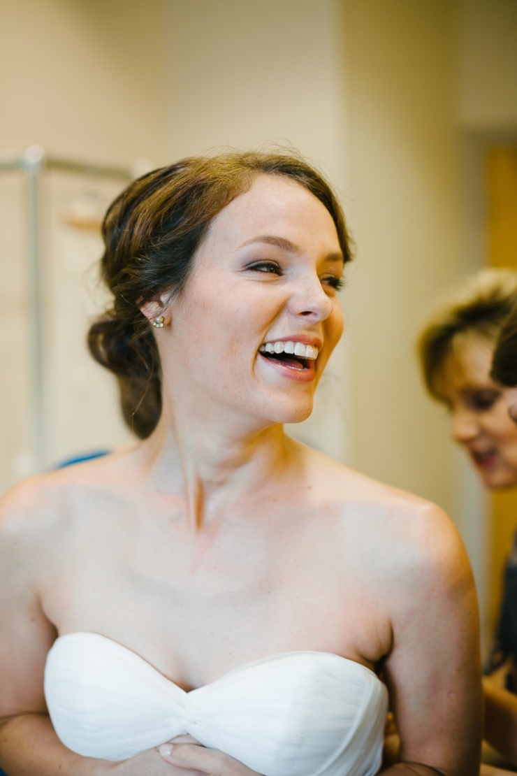 bride laughs after putting on wedding dress, wedding dress, Maggie Sottero gown, greenville sc wedding photographer, furman wedding, greenville wedding photography