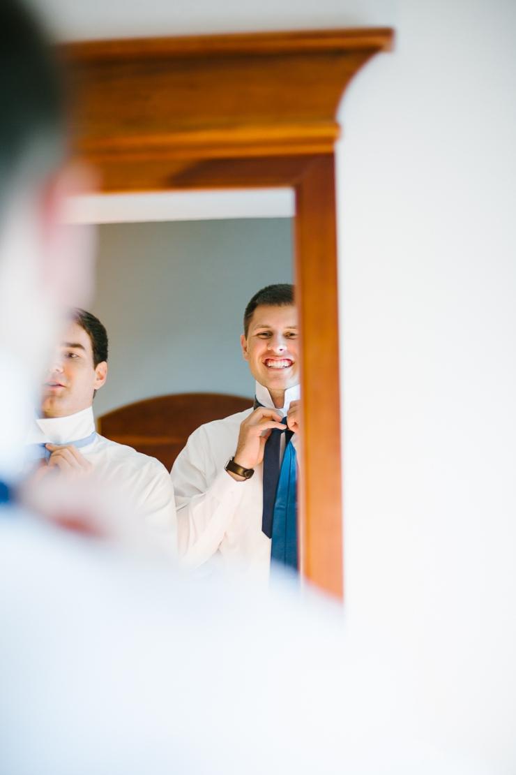 groom ties his blue tie on wedding day, Furman chapel, Furman wedding, greenville wedding photography