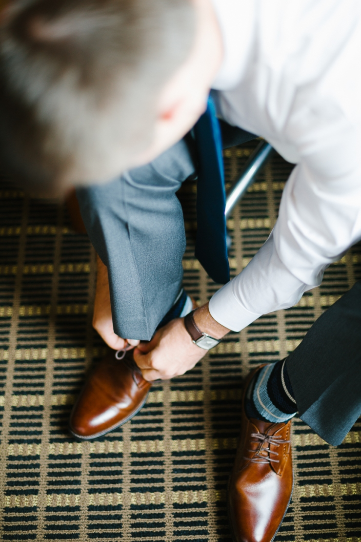 groom ties his shoes on wedding day, Furman chapel, Furman wedding, greenville wedding photography