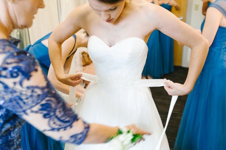 bride puts sash around her wedding dress, wedding dress, Maggie Sottero gown, greenville sc wedding photographer, furman wedding, greenville wedding photography