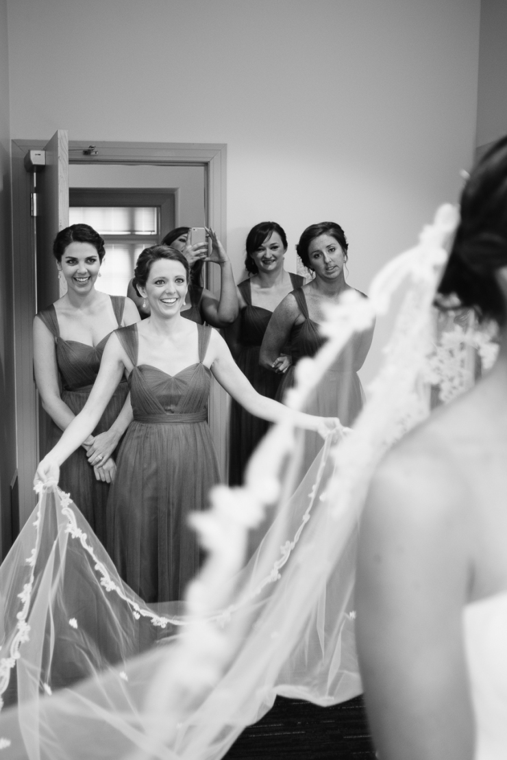 bridesmaids watch as bride puts on veil for her wedding, , wedding dress, mother's heirloom veil, Maggie Sottero gown, greenville sc wedding photographer, furman wedding, greenville wedding photography