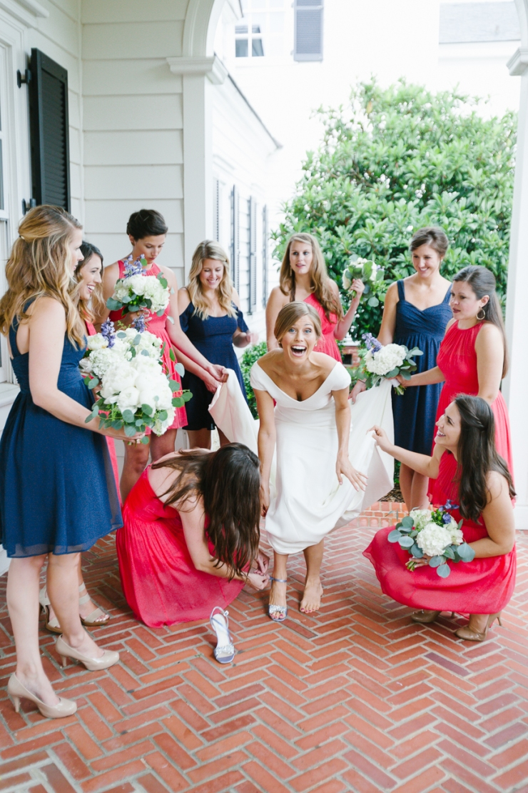 Bridesmaids help bride put on shoes before wedding in SC