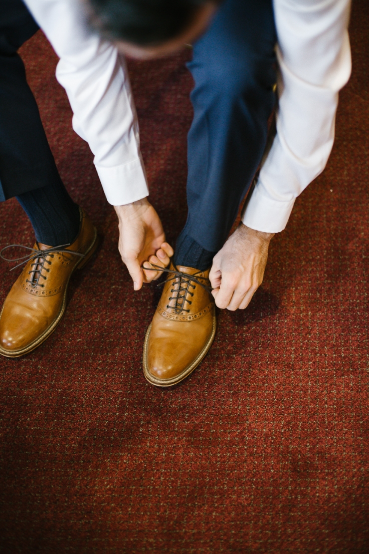 Groom ties his shoes as he gets ready for his wedding day