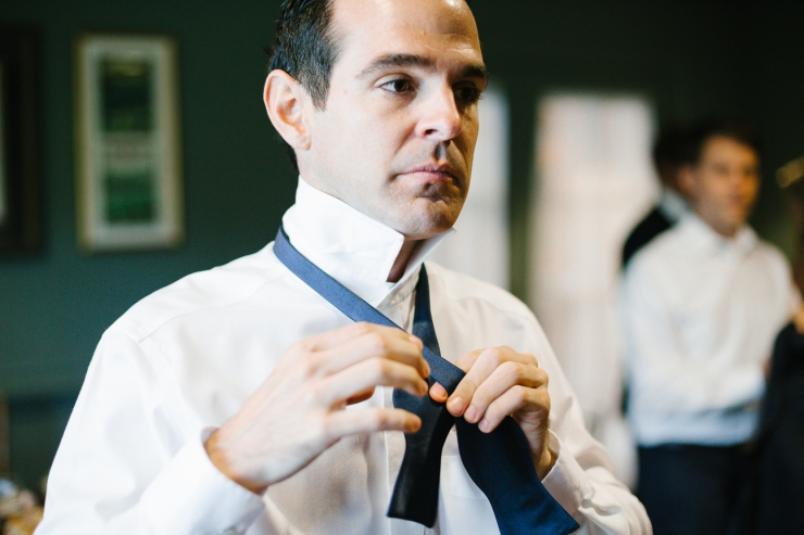 Groom ties his navy bowtie as he gets ready for his wedding day