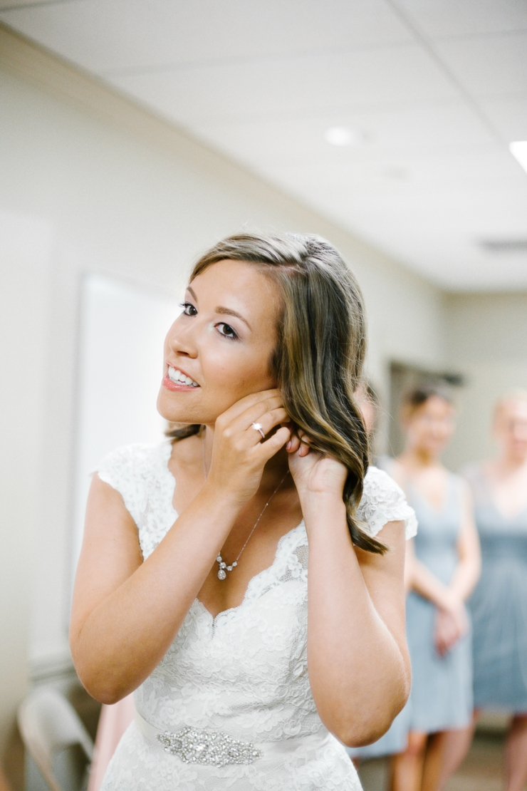 bride puts on wedding jewelry in Memphis TN