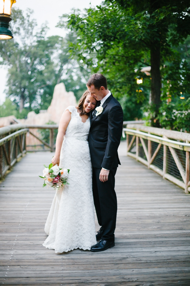 Bride and groom cuddle on bridge before entering their reception at Memphis zoo Teton Trek exhibit