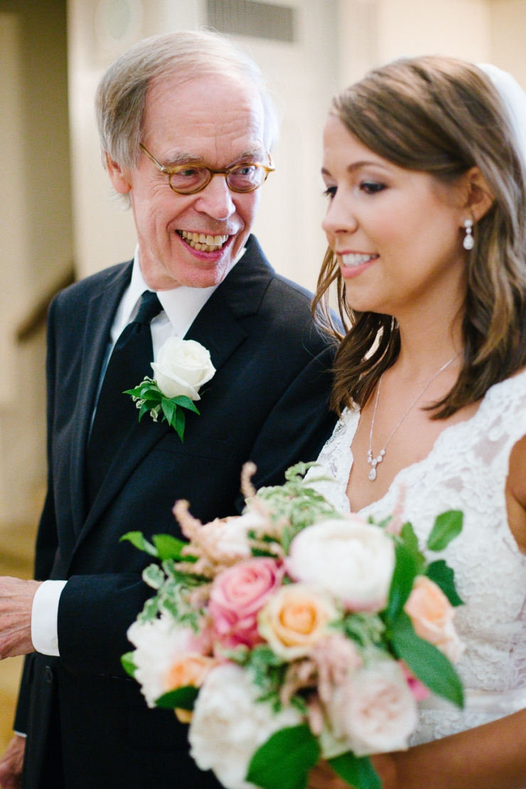 Father of bride looks at his daughter before walking her down the aisle