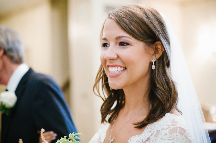 Bride smiles as she sees her future husband waiting at the altar