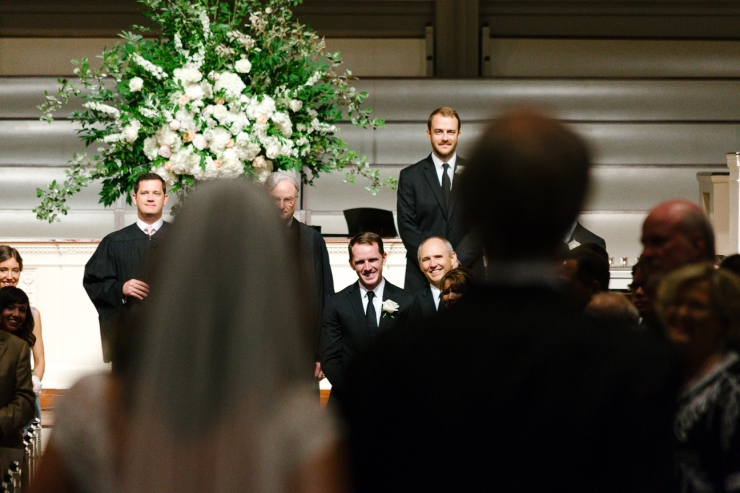 groom smiles as he sees his bride walking down the aisle