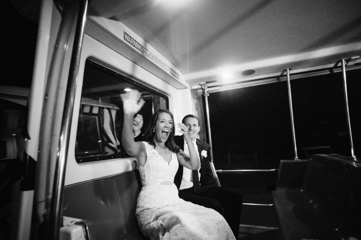 black and white image of bride and groom waving as they leave Memphis zoo in golf cart