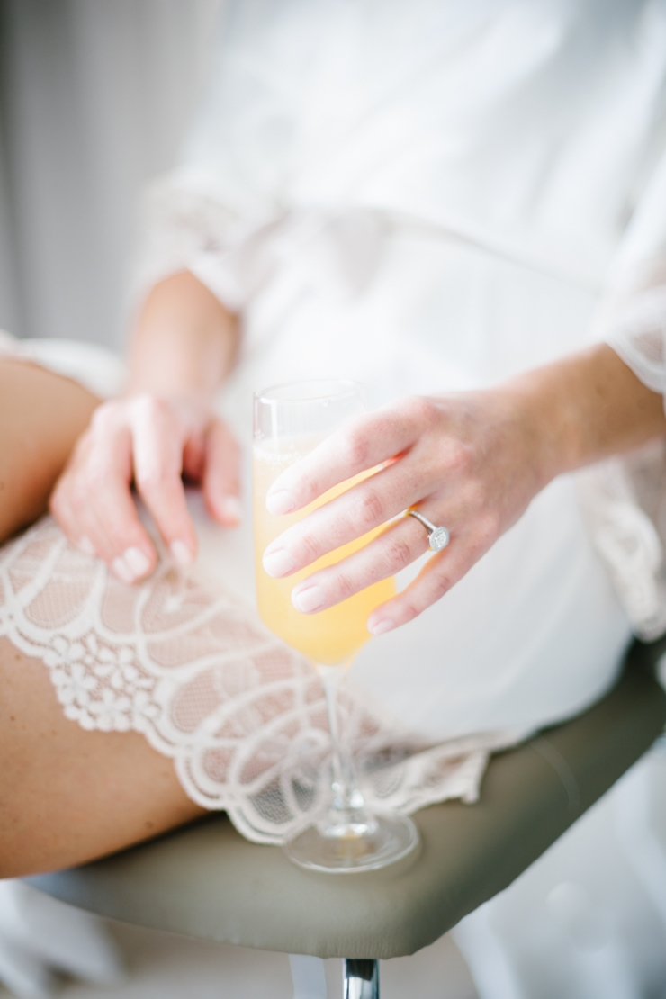 bride holds mimosa with champagne while getting ready for wedding day in Mexico