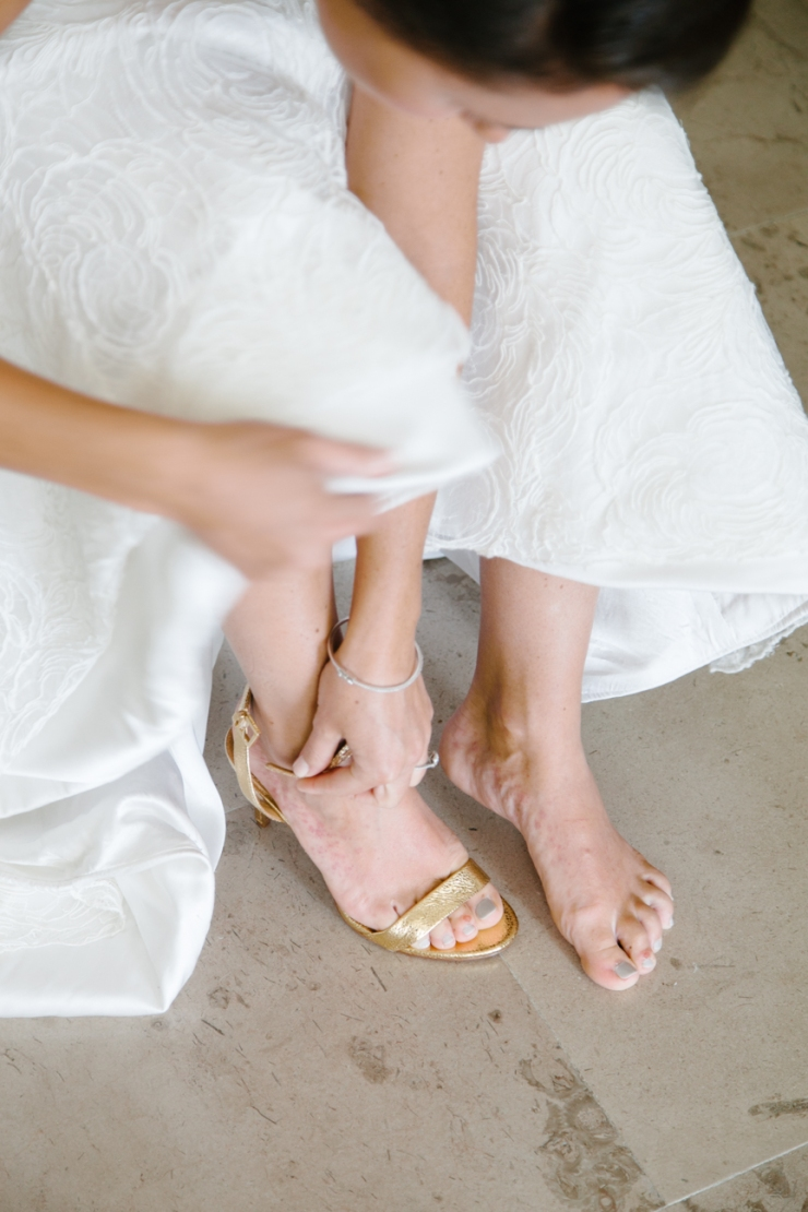bride puts on Tory Burch gold heels for wedding