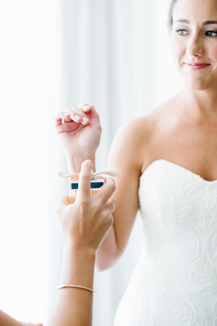 maid of honor sprays perfume onto bride's wrist on wedding day