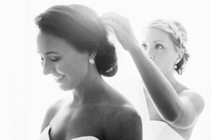 maid of honor puts veil into brides hair, black and white image