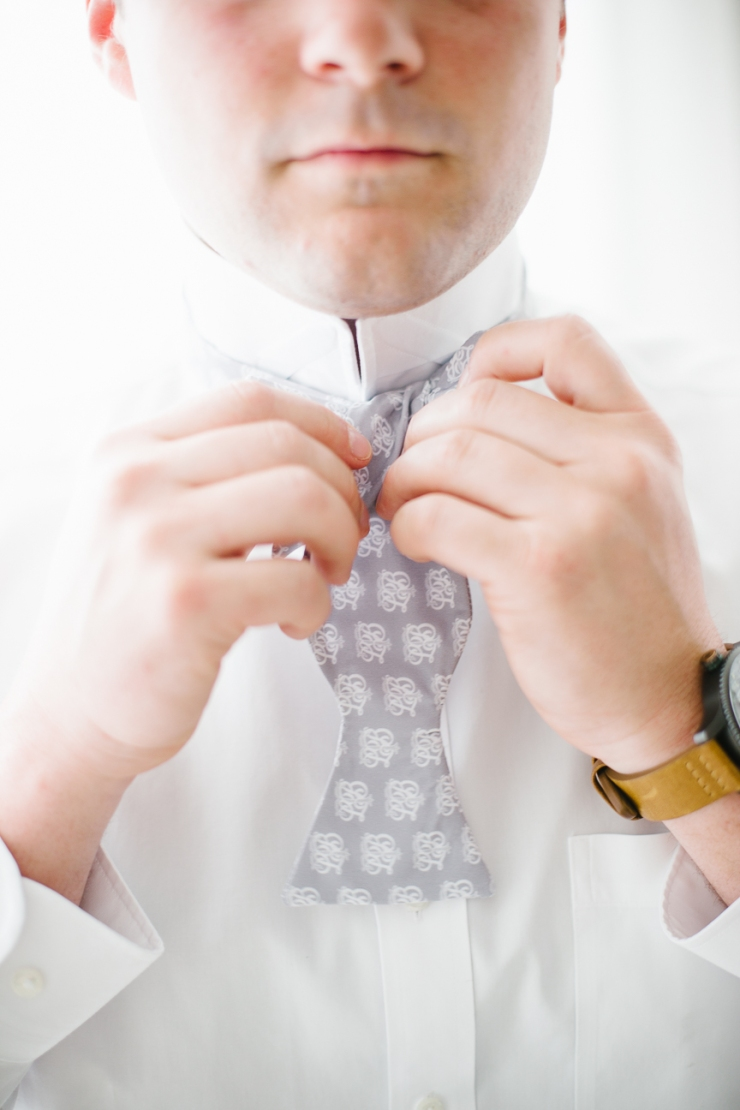 groom ties gray and white bowtie to get ready for his Mexico wedding