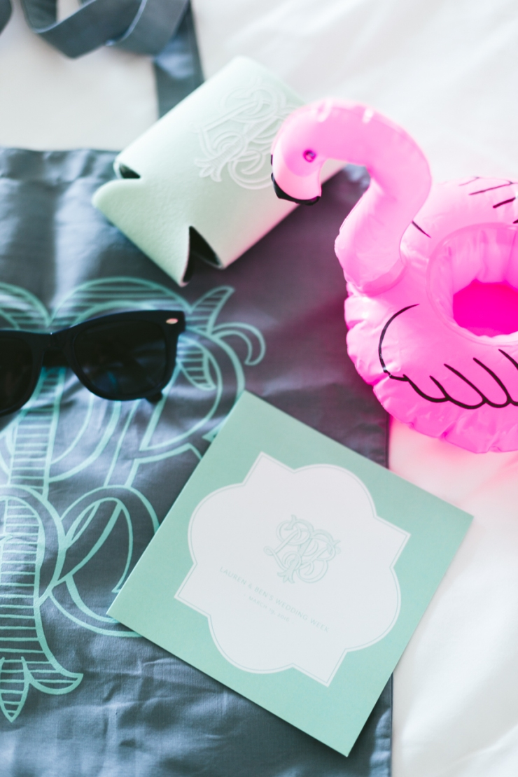 wedding welcome bag with inflatable drink flamingo, mint doozie, sunglasses, wedding itinerary, and monogrammed bag