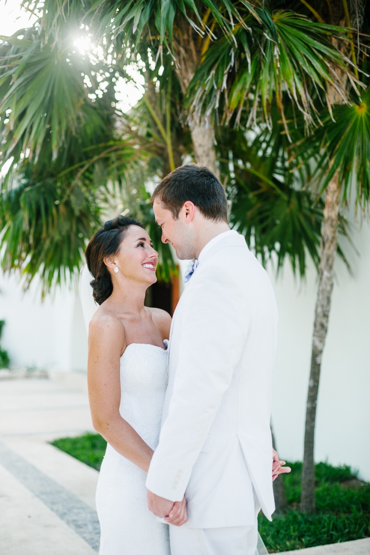 Bride and groom portrait under palm trees in Mexico