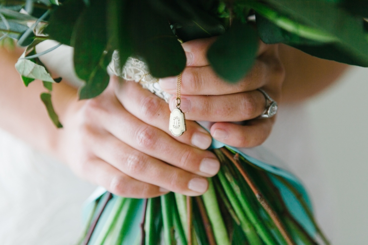 bride's hands holding bouquet and heirloom locket from her mother