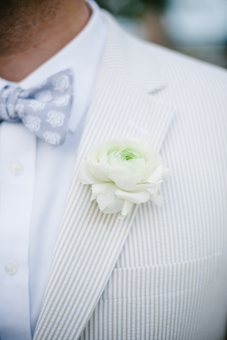 Groom's seersucker jacket, monogrammed bowtie, and white ranunculus boutonniere at Mexico wedding