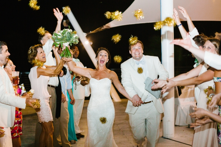 Couple departs from reception through a shower of gold pom poms, puffs, wedding exit