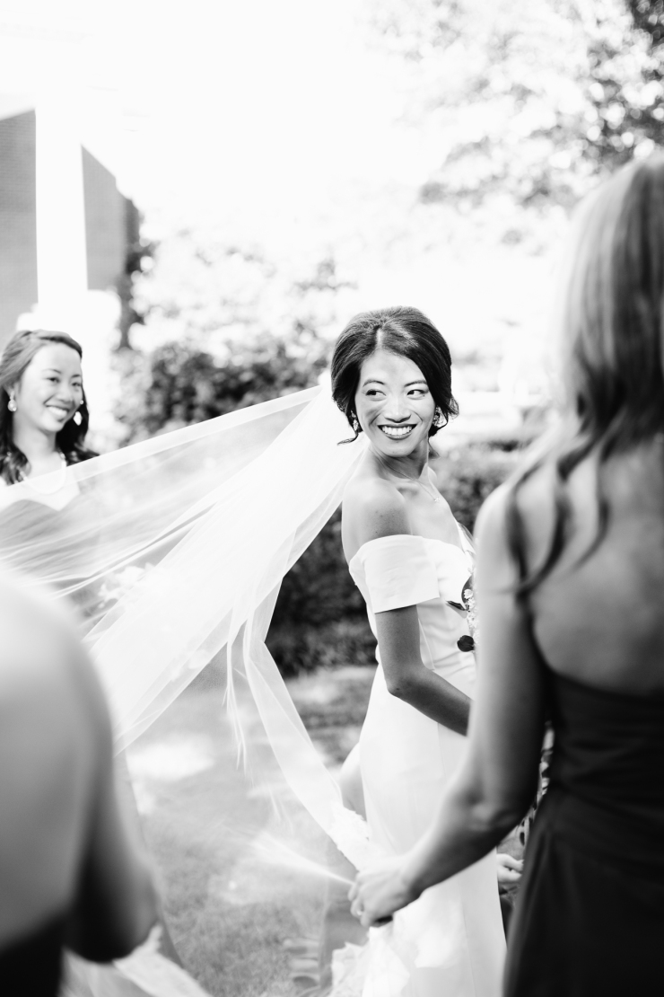 bride looks back at bridesmaid's fixing her veil, memphis tn wedding