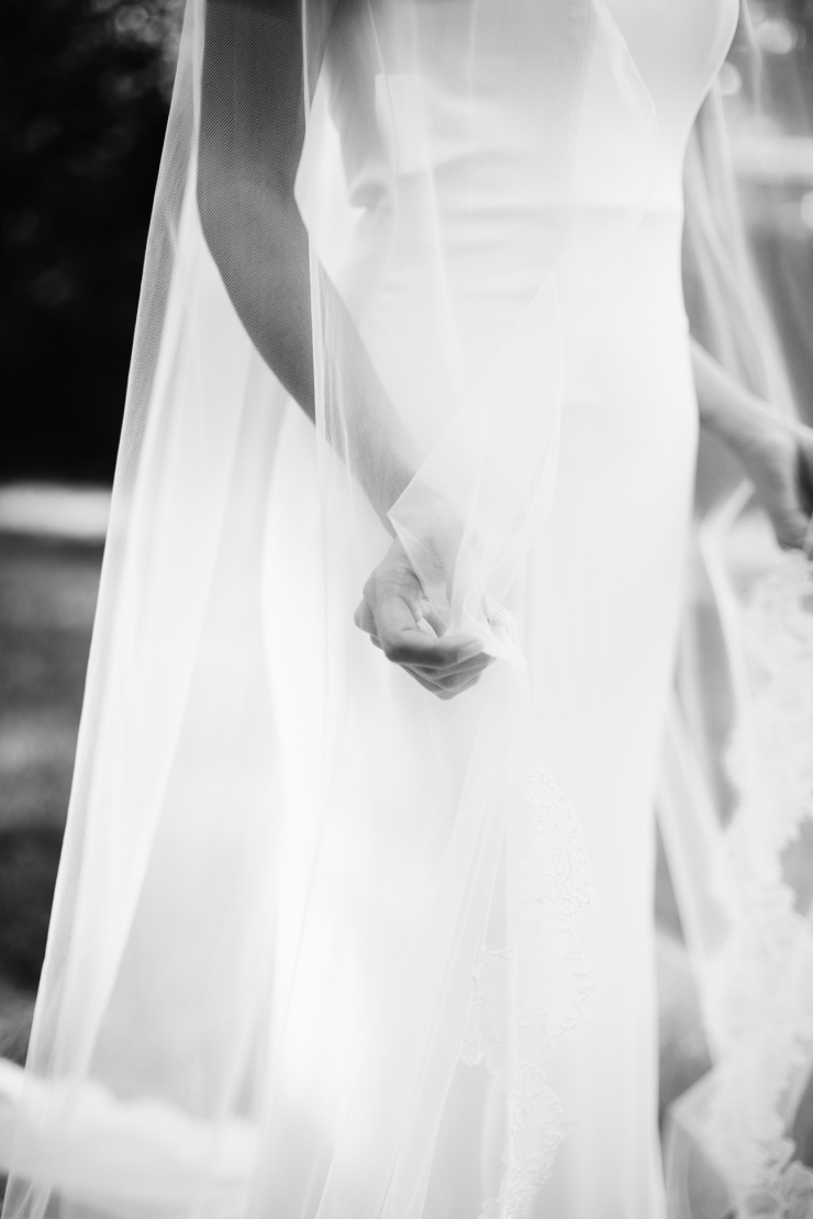 bride admires her lace veil, detail shots